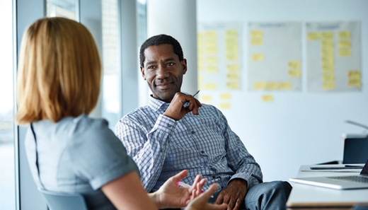 Man facing woman in a meeting room