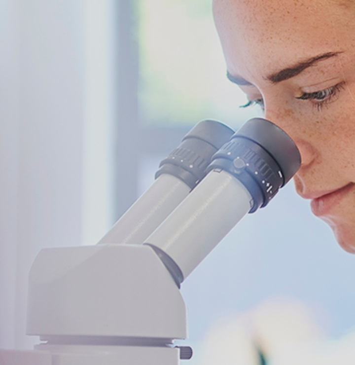 Researcher in lab looking down microscope